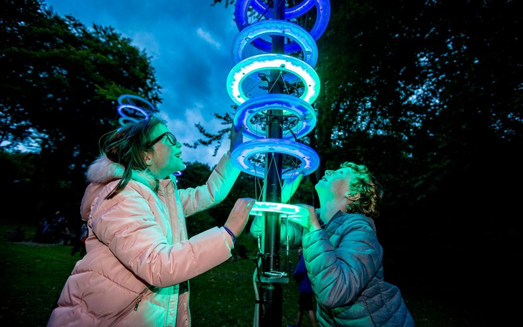 Two young children exploring a light sculpture