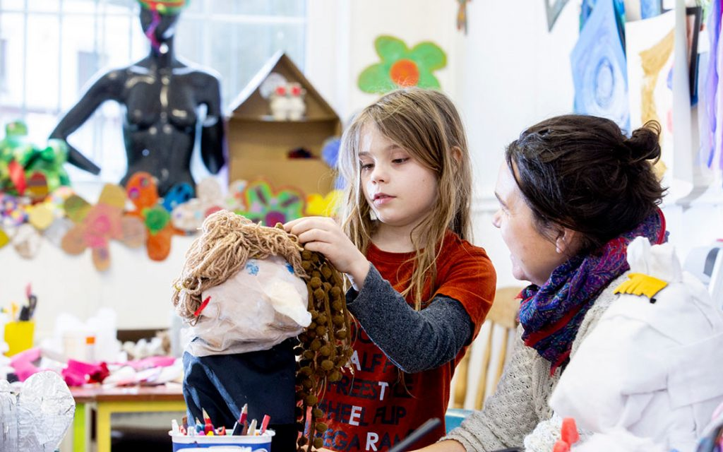 Young girl making a paper mache puppet